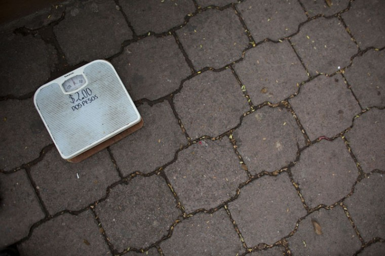 "A scale reading ""Two pesos"" (12 cents) lies on the ground in the main square in Iguala, Guerrero State, Mexico, Sunday, Sept. 27, 2015. An elderly man was using the scale to earn a meager income by charging passerby to weigh themselves.(AP Photo/Rebecca Blackwell)"