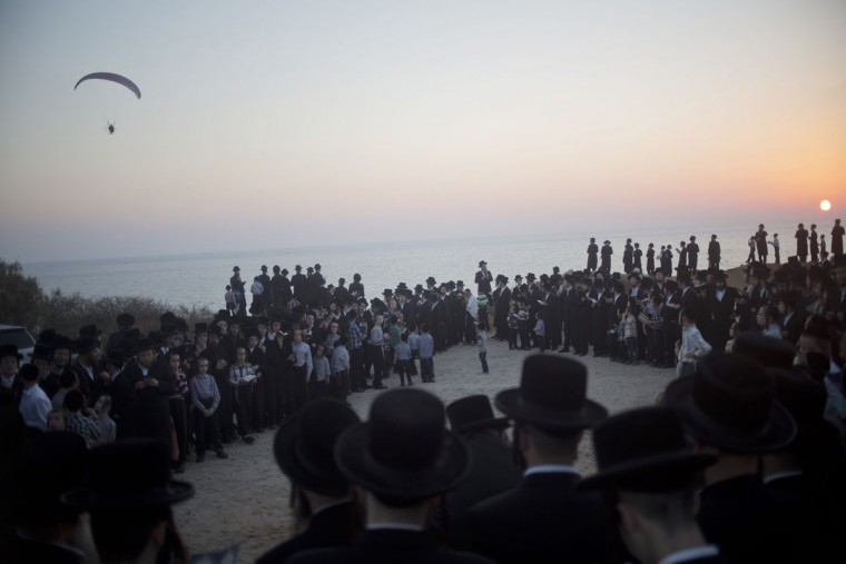 Ultra-Orthodox Jews of the Hassidic sect Vizhnitz listen to their rabbi on a hill overlooking the Mediterranean Sea as they participate in a Tashlich ceremony in Herzeliya, Israel, Monday, Sept. 21, 2015. (AP Photo/Ariel Schalit)