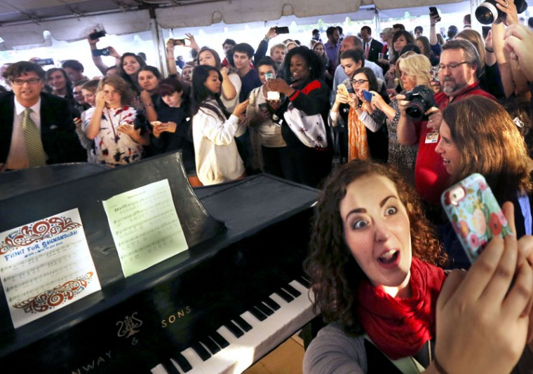 Shenandoah University junior Lindy Hockaday, right, takes a selfie with the cake in she shape and size of a Steinway grand piano that was made for the university's Ceremony of Celebration and Thanks for becoming an All-Steinway School Friday, Sept. 25. 2015 in Winchester, Virginia.(Scott Mason/The Winchester Star via AP)