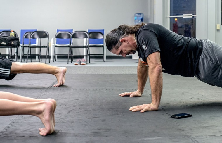 "Brian Arneson, 48, does a push-up during his black belt test at Elite Martial Arts Monday, Sept. 28, 2015, in Bridgewater, Va. Arneson has been training in martial arts ""off and on"" since he was 6. (Austin Bachand/Daily News-Record via AP)"