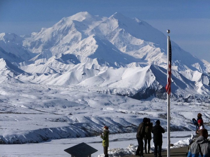 People stand at the Eielson Visitor Center with a view of North America's tallest peak, Denali, in the background, Wednesday, Sept. 2, 2015, in Denali National Park and Preserve, Alaska. The park covers more than 6 million acres, about the size of Vermont, and is an adventurer's paradise with few marked trails, inviting backcountry exploration. (AP Photo/Becky Bohrer)