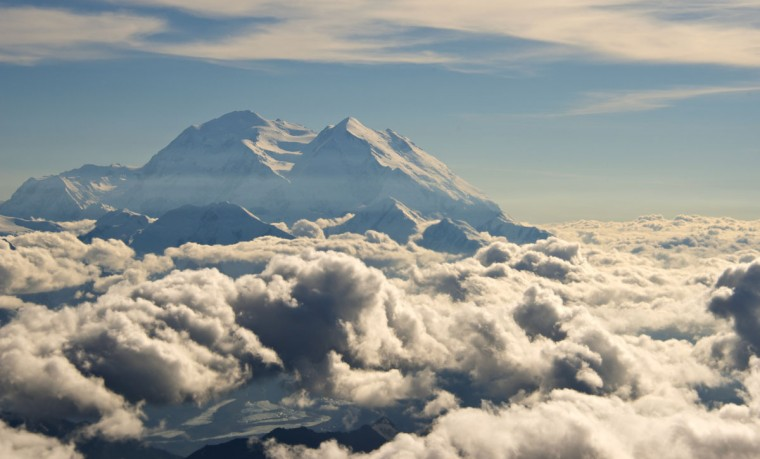 In this Monday, Aug. 3, 2015, aerial photo provided by Holland America Line, Mount McKinley pierces through the clouds above Denali National Park and Preserve in Alaska. On Sunday, Aug. 30, 2015, the White House said that President Barack Obama will change the name of North America's highest peak to Denali restoring an Alaska Native name with deep cultural significance. (Andy Newman/Holland America Line via AP)