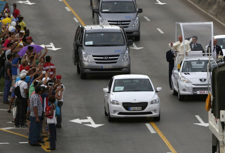 Pope Francis waves from his popemobile as he rides from the airport in Havana, Cuba, Saturday, Sept. 19, 2015. Pope Francis began his 10-day trip to Cuba and the United States, embarking on his first trip to the onetime Cold War foes after helping to nudge forward their historic rapprochement. (Enric Marti/Associated Press)