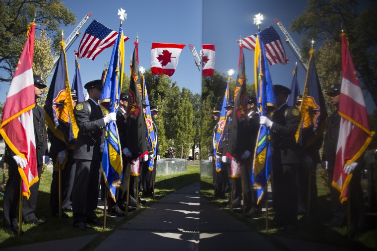 Honor Guard members are reflected in the Fallen Fire Fighter Memorial as they take part in the 29th annual IAFF Fallen Fire Fighter Memorial Service Saturday, Sept. 19, 2015, in Colorado Springs, Colo. (Mark Reis/The Gazette via AP)