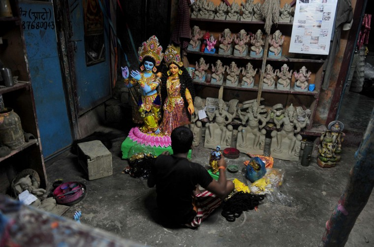 An Indian clay artisan works on an idol of Lord Krishna and Radha at a workshop, ahead of the upcoming festival of Janmashtami, in Allahabad on September 2, 2015. (Sanjay Kanojia/AFP/Getty Images)