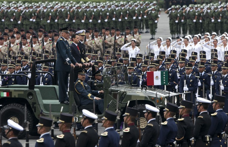 Flanked by his Secretary of Defense Gen. Salvador Cienfuegos Zepeda, left, and Secretary of the Navy Adm. Vidal Soberon Sanz, right, Mexico's President Enrique Pena Nieto rides in an open military vehicle during the Independence Day military parade in the capital's main plaza, the Zocalo, in Mexico City, Mexico, Wednesday, Sept. 16, 2015. Mexico celebrates the anniversary of its 1810 independence uprising. (AP Photo/Marco Ugarte)