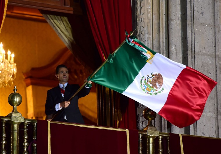 "Mexican President Enrique Pena Nieto waves the Mexican National Flag on the main balcony of the National Palace during ceremonies called ""The Shout"" marking the start of celebrations of Independence Day in Mexico City on September 15, 2015. (RONALDO SCHEMIDT/AFP/Getty Images)"