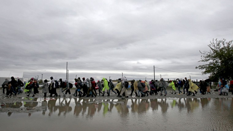 Migrants and refugees walk in the rain and cold towards the transit camp for refugees, just after crossing the border from Greece near the southern Macedonian town of Gevgelija, on Thursday, Oct. 22, 2015, as migrants make their way across Europe by the tens of thousands, fleeing war or seeking a better life. A U.N. refugee agency field officer says a large number of families with small children have been among the thousands of migrants and it is a tendency seen over the last couple of weeks. (AP Photo/Boris Grdanoski)
