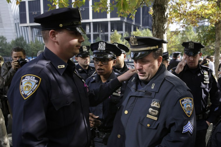 A police officer cries after laying flowers in memory of Officer Randolph Holder at the 9/11 Memorial in New York, Thursday, Oct. 22, 2015. Tyrone Howard is charged with first-degree murder and robbery, accused of stealing a bike and fatally shooting Holder in the head after a chase Tuesday night. (AP Photo/Seth Wenig)