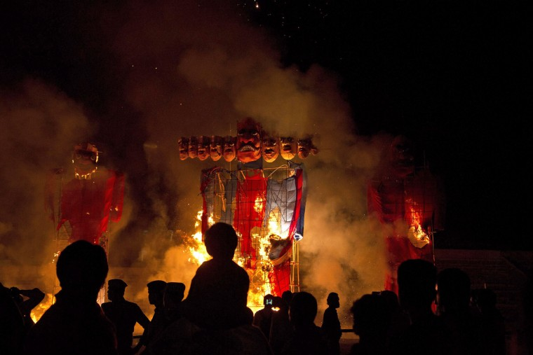 People watch effigies of the ten-headed demon king Ravana go up in flames during Dussehra celebrations in Gauhati, India , Thursday, Oct. 22, 2015. Dussehra festival commemorates the victory of Hindu god Rama over Ravana. The burning of effigies of Ravana, signifying the victory of good over evil, brings the festivities to a close. (AP Photo/ Anupam Nath)