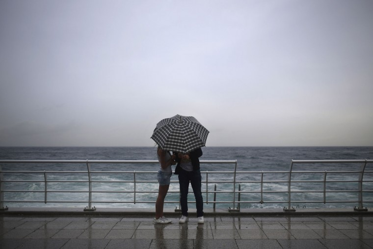 A Lebanese couple stand under an umbrella in rainy weather at the Corniche or waterfront promenade, in Beirut, Lebanon, Sunday, Oct. 25, 2015. (AP Photo/Hassan Ammar)