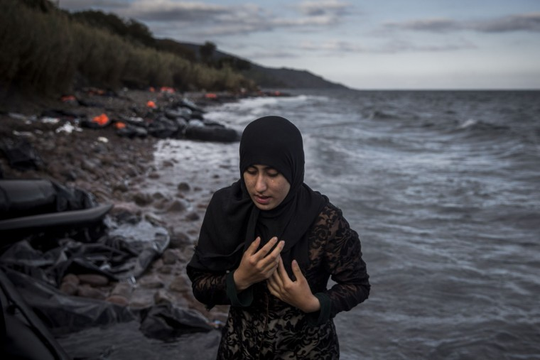 A woman cries after arriving at a beach by dinghy from a Turkish coast to the northeastern Greek island of Lesbos, Sunday, Oct. 25, 2015. The International Office for Migration says Greece over the last week experienced the largest single weekly influx of migrants and refugees this year, at an average of some 9,600 per day. (AP Photo/Santi Palacios)