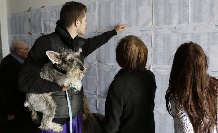 A voter holding his dog helps others find their names on voter lists during elections in Buenos Aires, Argentina, Sunday, Oct. 25, 2015. Argentines are weighing continuity versus a financial overhaul in Sunday's elections as they pick the successor to President Cristina Fernandez. (AP Photo/Jorge Saenz)