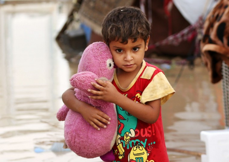 Omar Abdullah, 5, holds a stuffed animal outside his tent submerged in rainwater at a camp for displaced persons in Youssifiyah, 12 miles (20 kilometers) south of Baghdad, Iraq, Thursday, Oct. 29, 2015. Rain storms began late day Wednesday and continued through the morning Thursday, dumping heavy rain on the Iraqi capital and across the country. The Iraqi government declared Thursday a holiday to ease the burden on people who may otherwise struggle to get to work. (AP Photo/Hadi Mizban)