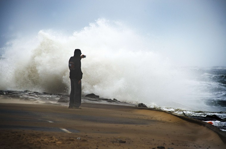 A tourist watches as waves batter the beach in Ocean City, Maryland, on October 3, 2015. According to local weather reports, coastal flooding warnings have been issued along the US east coast as heavy rains, partly fueled by Hurricane Joaquin, continue to fall on the area. Joaquin, a category 3 hurricane, is forecast to veer away from the US, moving toward the northeast at 13 mph (20 km/h), according to the National Hurricane Center. (Jim Watson/AFP Getty Images)