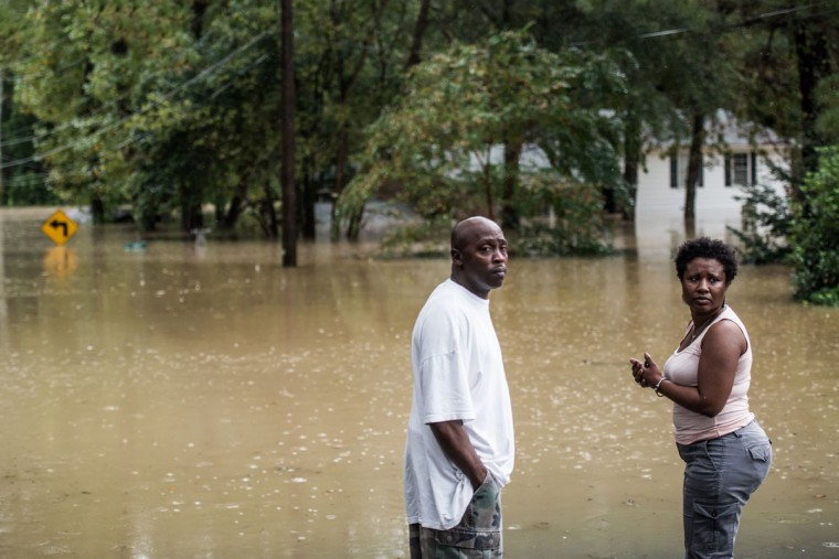 Farrell Rose and his fiancee Damita Trapp look away after flood waters surrounded their home October 4, 2015 in Columbia, South Carolina. (Photo by Sean Rayford/Getty Images)