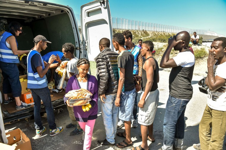 "This file photo taken on August 8, 2015 shows migrants waiting to receive food from the humanitarian organization ""L'Auberge des Migrants"" at the entrance of the migrant camp dubbed 'New Jungle' in Calais, northern France. (PHILIPPE HUGUEN/AFP/Getty Images)"