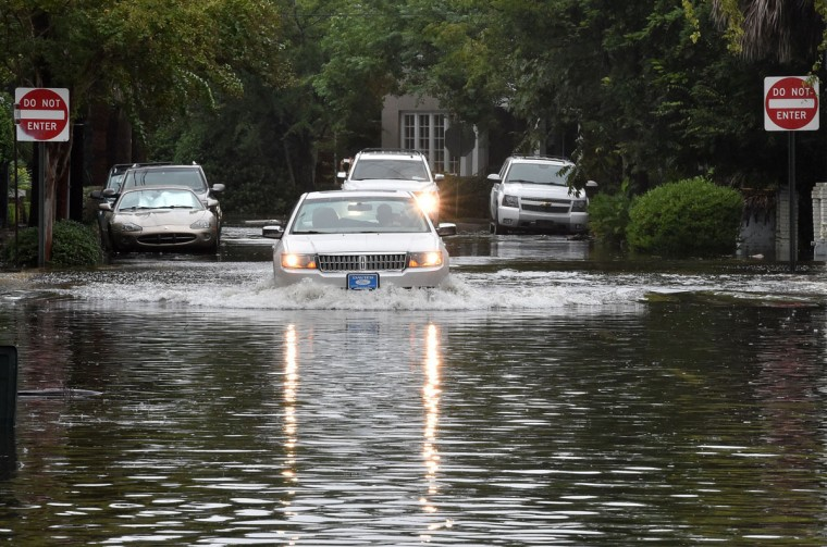 A car drives down a flooded street in Charleston, South Carolina on October 4, 2015. (MLADEN ANTONOV/AFP/Getty Images)