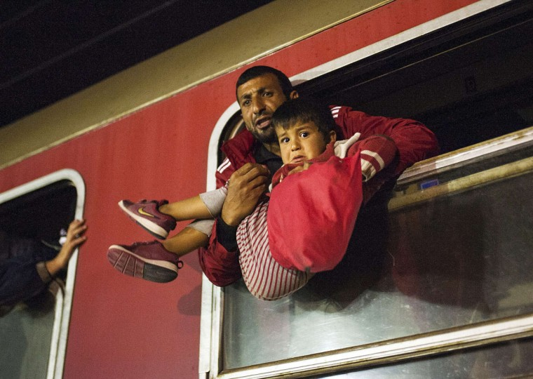 A man holds a child in a train heading to Serbia from the Macedonian-Greek border near Gevgelija on October 6, 2015. Macedonia is a key transit country in the Balkans migration route into the European Union, with thousands of asylum seekers and migrants - many of them from Syria, Afghanistan, Iraq and Somalia - entering the country every day. The EU said a controversial programme to relocate 40,000 refugees within the bloc from overstretched frontline states would formally start on October 9 when a group of Eritreans will travel to Sweden from Italy. (AFP Photo/Robert Atanasovski)