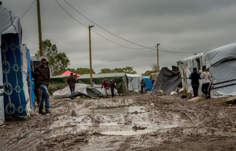 "People stand on a site dubbed the ""New Jungle,"" where some 3,000 people have set up camp -- most seeking desperately to get to England, in Calais on October 7, 2015. (PHILIPPE HUGUEN/AFP/Getty Images)"