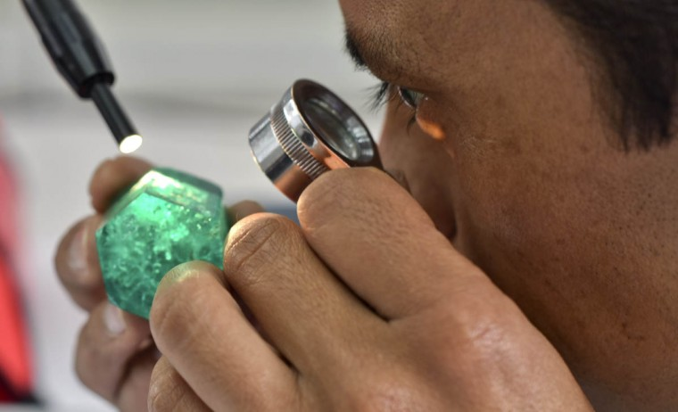 A worker looks at an emerald at the workshop of Muzo Emerald Company in Bogota. (Luis Acosta/Getty Images)