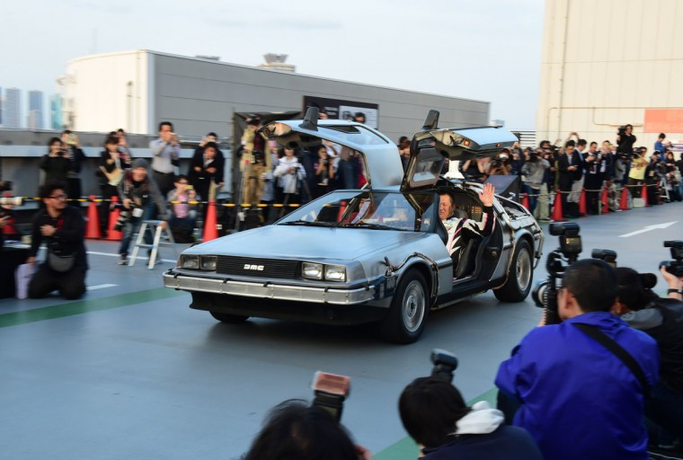"A ""Back to the Future"" style DeLorean, powered by methanol bio-fuel made from recycled clothing produced by a Japanese venture, runs before hundreds of movie fans on the rooftop of a shopping mall in Tokyo on October 21, 2015 for the 30th anniversary of the Hollywood movie ""Back to the Future"". (AFP Photo/Yoshikazu Tsuno)"