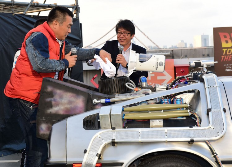 "ironment Planning president Michihiko Iwamoto (R) and former baseball player Masa Yamamoto throw a tee-shirt into the ""Mr. Fusion Home Energy Reactor"" compartment of a ""Back to the Future"" style DeLorean, powered by methanol bio-fuel made from recycled clothing produced by a Japanese venture, as the vehicle is displayed before hundreds of movie fans on the rooftop of a shopping mall in Tokyo on October 21, 2015 for the 30th anniversary of the Hollywood movie ""Back to the Future"". (AFP Photo/Yoshikazu Tsuno)"