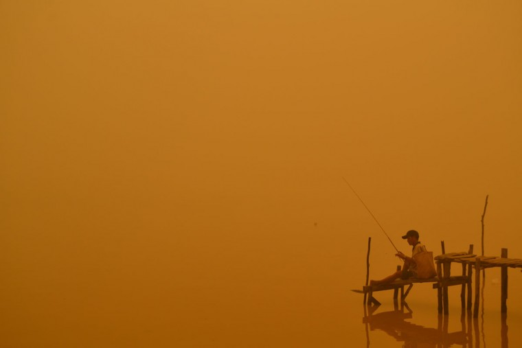 A resident fishes by the river in Palangkaraya city, one of worst-hit by haze in central Kalimantan province, on October 21, 2015. Indonesian forest and agricultural fires cloaking Southeast Asia in acrid haze are spewing more greenhouse gases into the atmosphere each day than all US economic activity, according to an environmental watchdog. (HARIS SADIKIN/AFP/Getty Images)