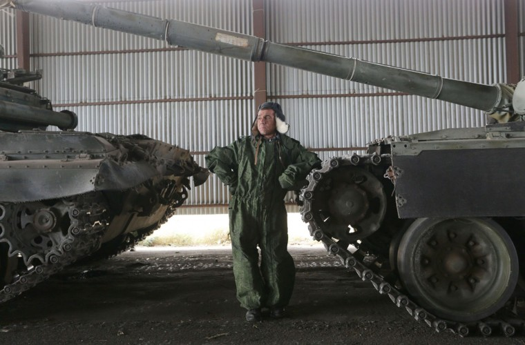 A pro-Russian separatists soldiers stands next to T-72 battle tanks parked in a warehouse away from the frontline, after being withdrawn from their positions near the town of Novoazovsk in the Donetsk region on October 21, 2015. Ukrainian forces and pro-Russian insurgents said today they had begun withdrawing tanks and smaller weapons from the front line in the devastated Donetsk region in the ex-Soviet state's eastern war zone. (AFP Photo/Aleksey Filippov)