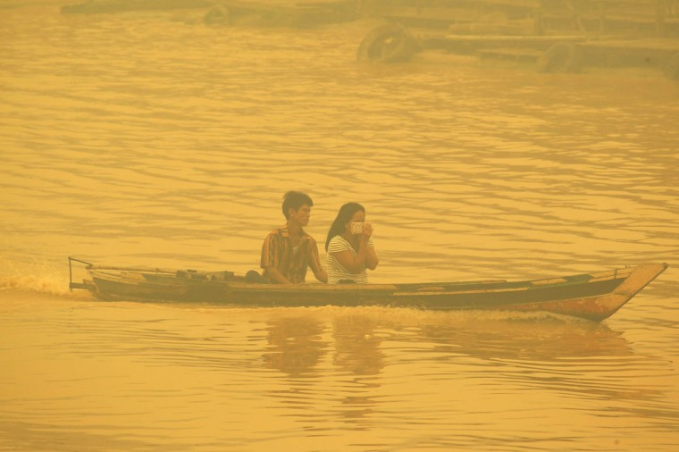A couple crosses a river by boat as the city shrouded in thick yellow haze in Palangkaraya on October 22, 2015. Dense haze from Indonesian forest fires has caused some of the worst pollution in southern Thailand for a decade, officials said October 22, cancelling flights in an area popular with tourists. (WISANGGENI/AFP/Getty Images)