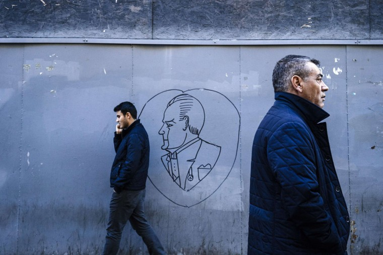 Men walk past a drawing on wall featuring the founder of the Turkish republic, Mustafa Kemal Ataturk in downtown Istanbul on October 28, 2015, a week ahead of the country's general elections on November 1. The vote was called after the Justice and Development Party (AKP), indomitable for 13 years, lost its majority in a June election and then failed to form a power-sharing government. (AFP Photo/Dimitar Dilkoff)