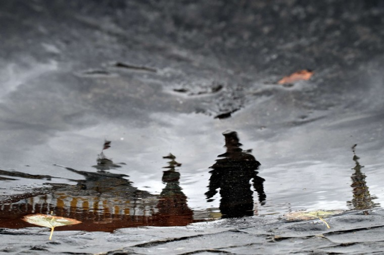 A man is reflected in a puddle as he walks across Moscow's Red Square on October 28, 2015. (AFP Photo/Kirill Kudryavtsev)