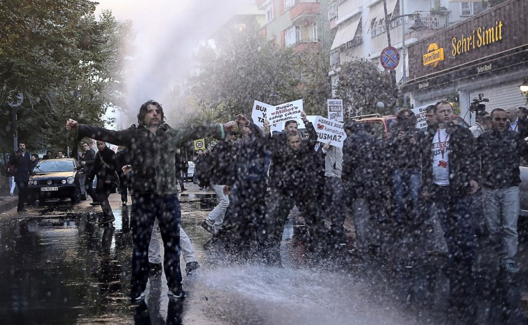 Turkish police use a water cannon to disperse supporters and employees of Bugun newspaper and Kanalturk television station during a protest in Istanbul on October 28, 2015 against the Turkish government's crackdown on media outlets. Riot police firing tear gas and water cannon on October 28 stormed the Istanbul headquarters of a media group linked to President Recep Tayyip Erdogan's bitter rival, on what was described as a dark day for democracy ahead of a pivotal election. Officers smashed through the gates of the media compound with chainsaws, according to images broadcast live on the group's television stations, Bugun and Kanalturk. (AFP Photo/Usame Zaman)