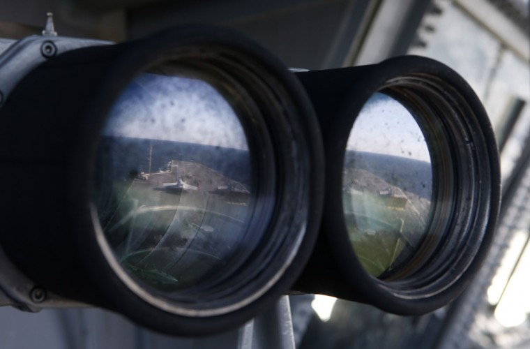 The deck of the USS Ronald Reagan, a Nimitz-class nuclear-powered aircraft carrier, is reflected in a pair of binoculars during a joint naval drill between South Korea and the US in the West Sea off South Korea on October 28, 2015. (AFP Photo / Hong-JiKim)