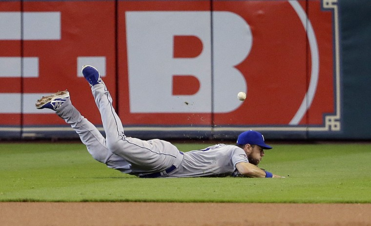 Kansas City Royals' Ben Zobrist dives for a hit by Houston Astros' Colby Rasmus during first inning in Game 4 of baseball's American League Division Series, Monday, Oct. 12, 2015, in Houston. (AP Photo/David J.Phillip)