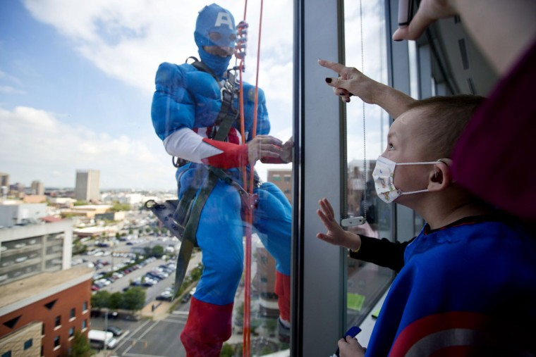 Landon Fox, 5, of Birmingham, looks up to see his favorite superhero, Captain America, a window washer dressed as a superhero at Benjamin Russell Hospital for Children, Wednesday, Oct. 7, 2015, in Birmingham, Ala. (AP Photo/Brynn Anderson)