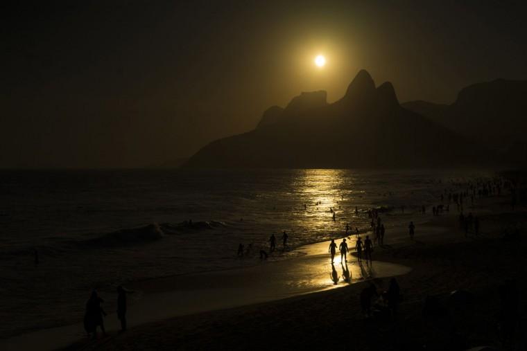 People walk at dusk in Arpoador beach, Rio de Janeiro, Brazil, Thursday, Oct. 15, 2015. (AP Photo/Felipe Dana)
