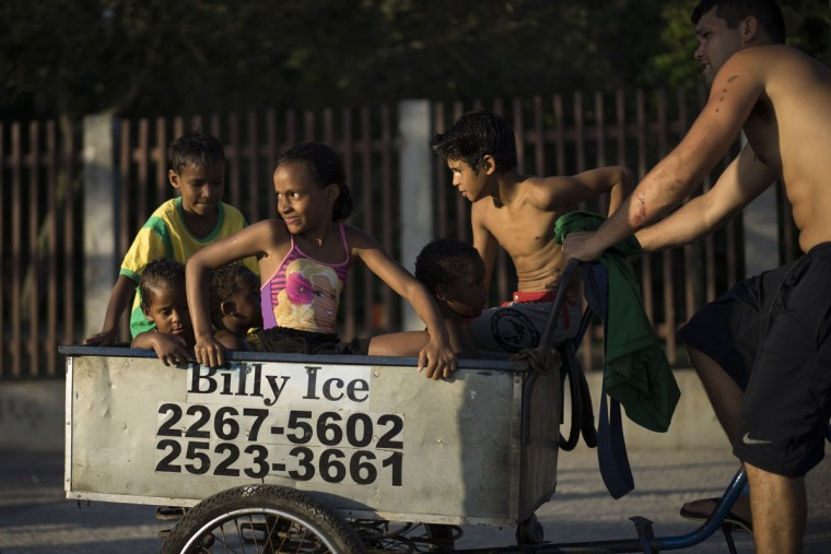 A man carries children on a bicycle cart on their way out of Arpoador beach in Rio de Janeiro, Brazil, Thursday, Oct. 15, 2015. (AP Photo/Felipe Dana)