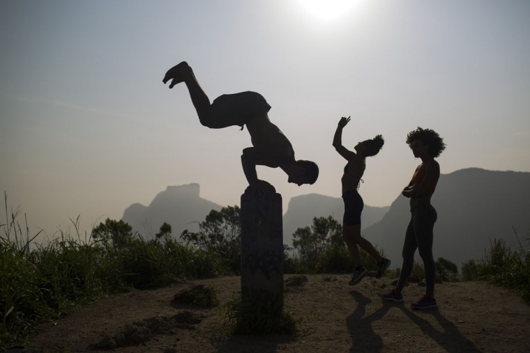 People exercise on the Morro Dois Irmaos or Two Brothers Mountain, atop the Vidigal slum in Rio de Janeiro, Brazil, Friday, Oct. 2, 2015. Despite the recent wave of violence in other pacified favelas, Vidigal has been peaceful and is today a popular tourist spot. (AP Photo/Felipe Dana)