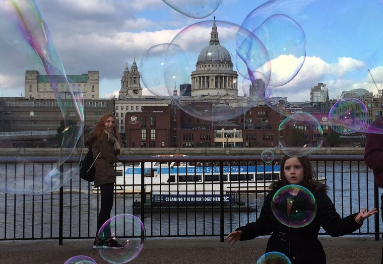 Tourists watch soap bubbles along the Thames river, London, backdropped by St. Paul's Cathedral, Tuesday, Oct. 20, 2015. (AP Photo/Christophe Ena)