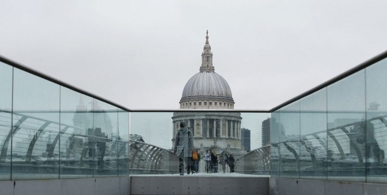 Pedestrians are reflected in the glass as they cross over the Millennium Bridge in front of St Paul's Cathedral in the City of London, Wednesday, Oct. 7, 2015. (AP Photo/Alastair Grant)