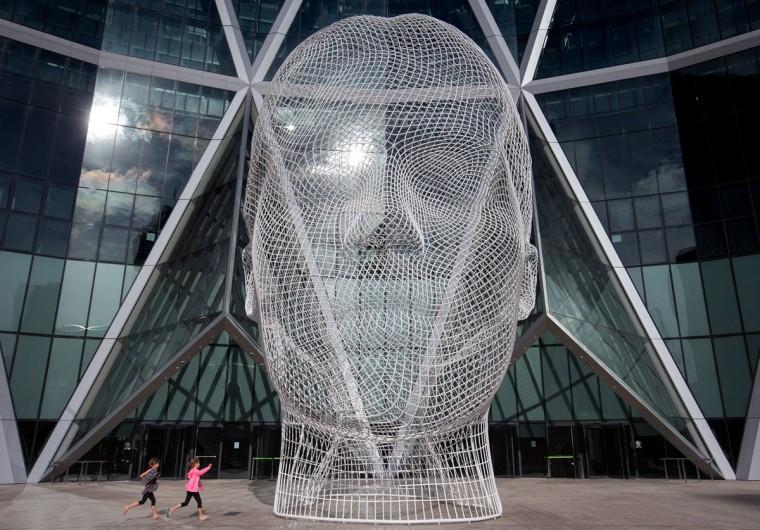"Children run near the sculpture ""Wonderland"" by Spanish artist Jaume Plensa, Sunday, Oct. 18, 2015, 2015, in downtown Calgary, Alberta. (Darryl Dyck/The Canadian Press via AP)"