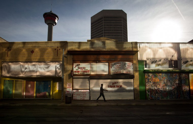 A man walks as sunlight reflects off the windows of an office building Sunday, Oct. 18, 2015, 2015, in downtown Calgary, Alberta. (Darryl Dyck/The Canadian Press via AP)