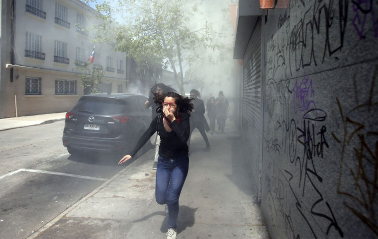 A protester runs from tear gas fired by police at the end of a student march in Santiago, Chile, Thursday, Oct. 15, 2015. Demonstrators marched to complain about delays in an education overhaul and ask President Michelle Bachelet to fulfill her campaign promise of free education. (AP Photo/Luis Hidalgo)