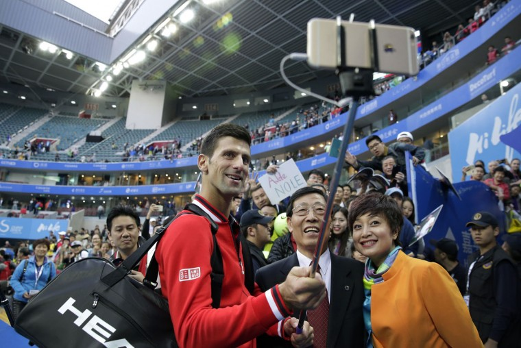 Novak Djokovic of Serbia, center, takes a selfie with officials after winning his men's singles match against Zhang Ze of China in the China Open tennis tournament at the National Tennis Stadium in Beijing, Thursday, Oct. 8, 2015. (AP Photo/Andy Wong)