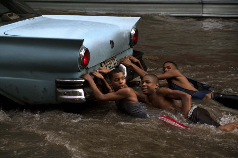 Youths hang from the rear bumper of a vintage American car as they play in a flooded street, after a heavy rain in Havana, Cuba, Wednesday, Oct. 14, 2015. (AP Photo/Ramon Espinosa)