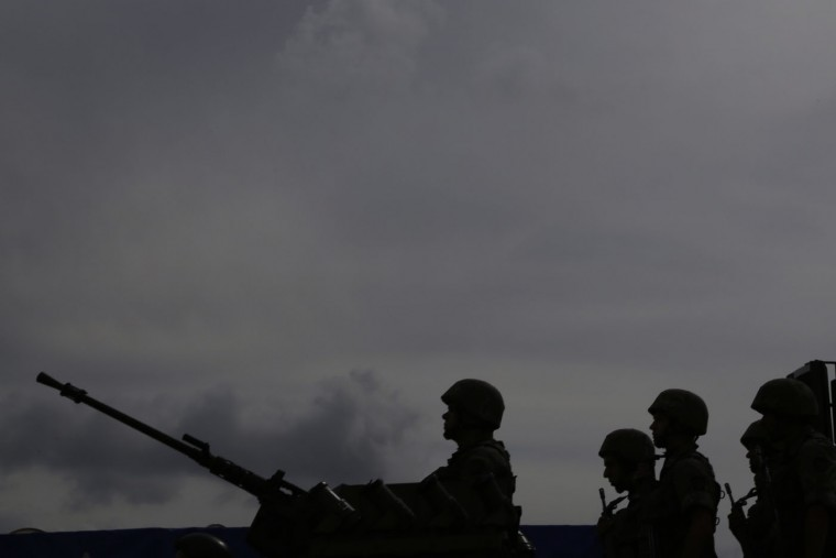 Cypriot soldiers in silhouettes stand on an armored military vehicle during the annual Cyprus Independence Day military parade in the divided capital of Nicosia, Thursday, Oct.1, 2015. Divided Cyprus is celebrating 55 years of independence amid peace talks to decide whether rival Greek and Turkish communities will herald the birth of a future unified state. The island of Cyprus has been divided since 1974, when Turkey invaded in response to a coup aimed at uniting the island with Greece. Cyprus gained independence from Britain in 1960. (AP Photo/Petros Karadjias)