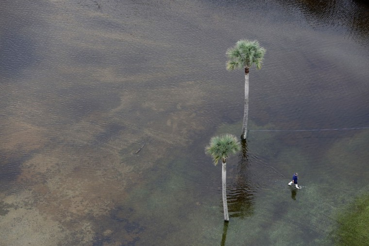 A man makes his way through floodwaters in the parking lot of The Citadel Beach Club on Isle of Palms, S.C., Monday, Oct. 5, 2015. The Charleston and surrounding areas are still struggling with flood waters due to a slow moving storm system. (AP Photo/Mic Smith)