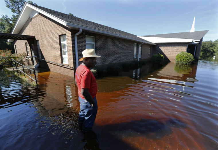 Harold Ancrum, a church member at Canaan United Methodist Church, checks on the floodwaters at the church near Summerville, S.C., Thursday, Oct. 8, 2015. The church had some caskets come out of the ground at their cemetery beside the church during the flooding this week. (AP Photo/Mic Smith)