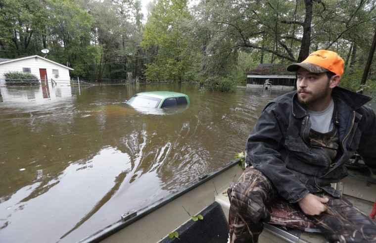 Hunter Baker surveys flood damage to his neighborhood near the flooded Black Creek following heavy rains in Florence, S.C., Monday, Oct. 5, 2015. Flooding continues throughout the state following record rainfall amounts over the last several days. (AP Photo/Gerry Broome)